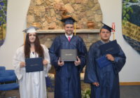Three smiling graduates celebrate as they are presented with high school diplomas from Longview School in Deerfield NH